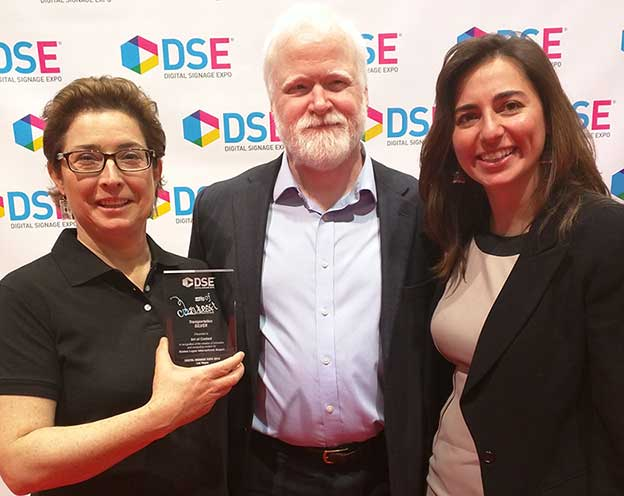 Art of Context Principals Colleen Hamilton and Tim Laughlin show off their silver award for digital signage content at DSE 2015 with Boston Logan Representative Itati Moguilner