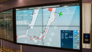 Close up of InfoWall a 2x2 map of Logan Airport featuring Interactive Wayfinding and a boarding pass scanner.